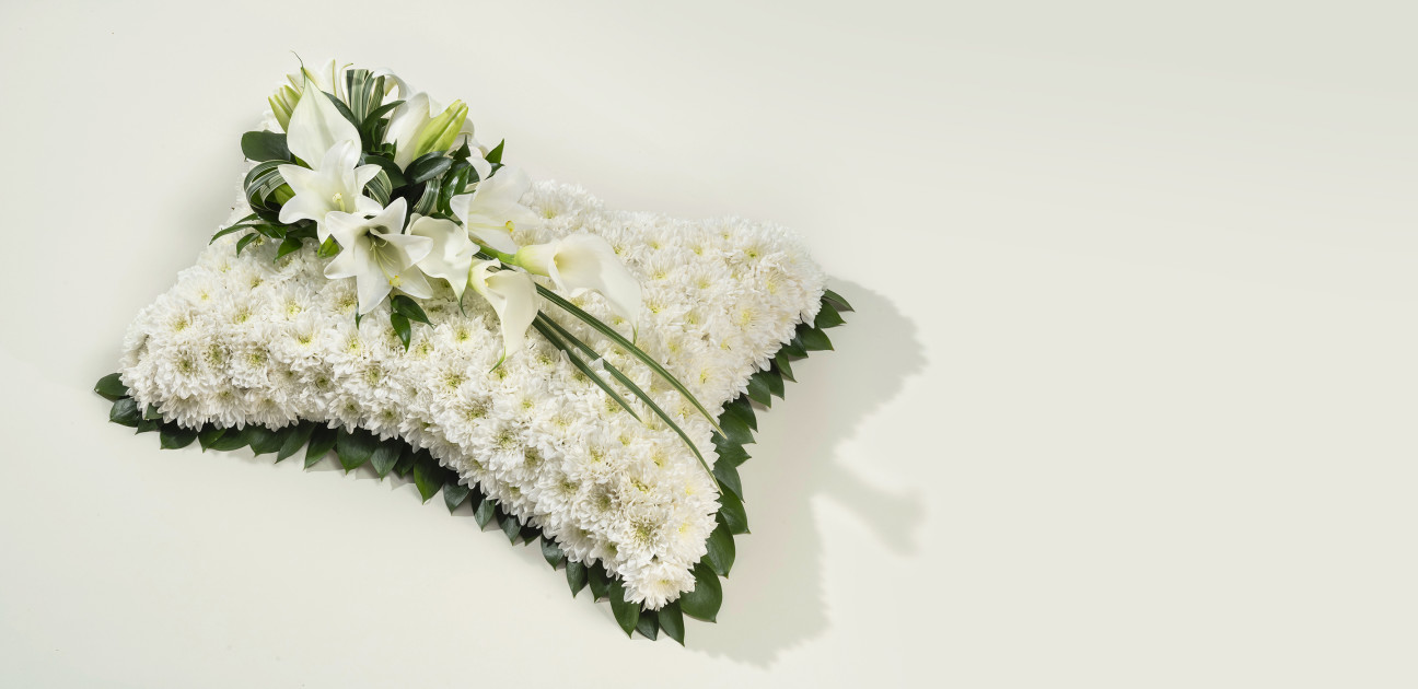 White pillow floral arrangement with lilies