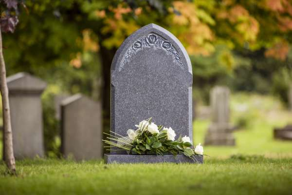 Grey natural headstone with white flowers laid.
