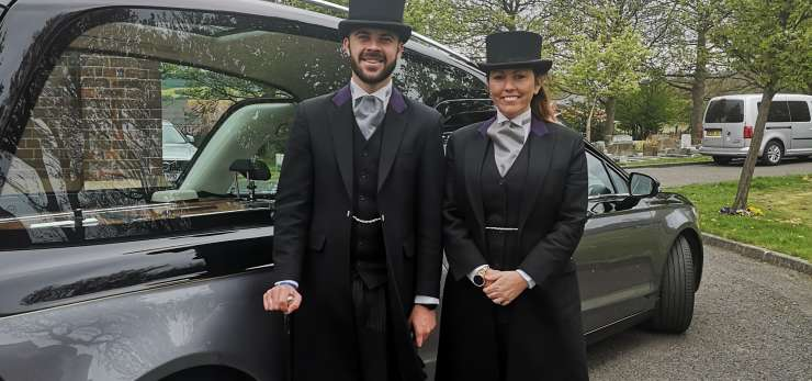 Husband and wife stood in front of a hearse.