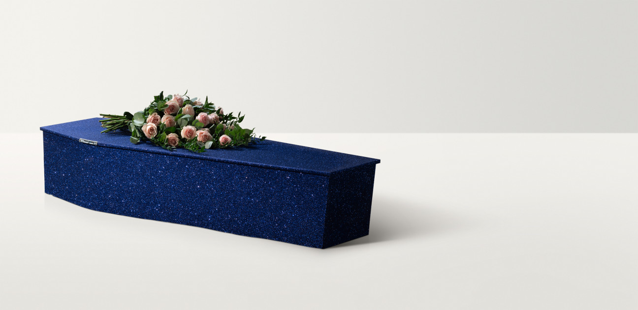 Midnight blue coffin with silver glitter and a pink floral arrangement on top