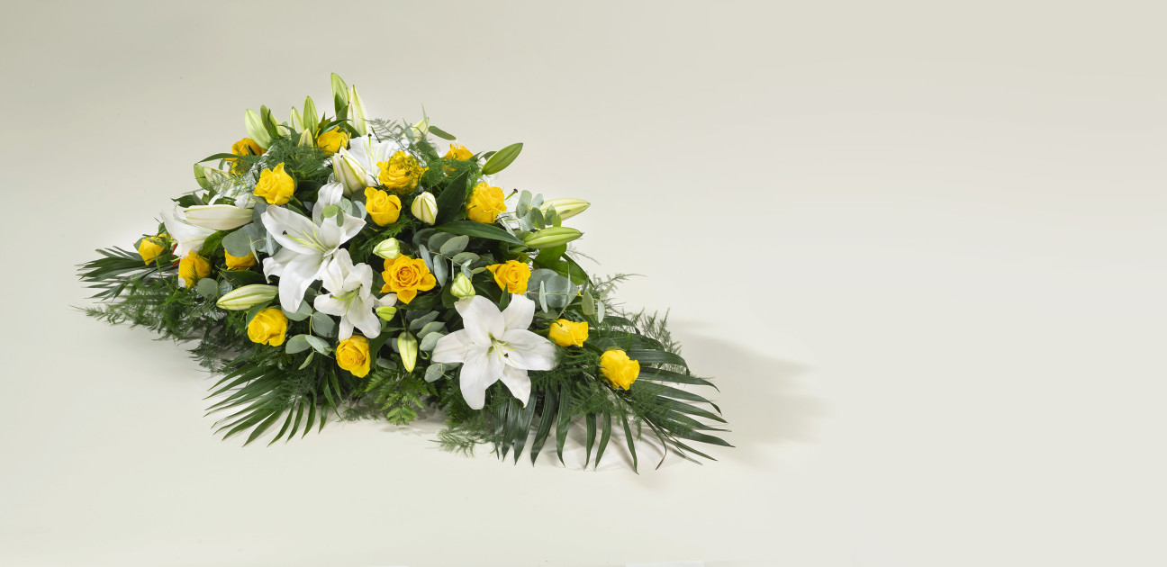 Spray shaped floral arrangement with white lilies and yellow roses on green foliage