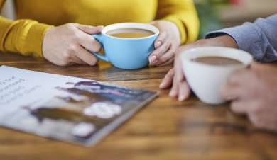 Couple sat at a table with cups of coffee discussing funeral plans.