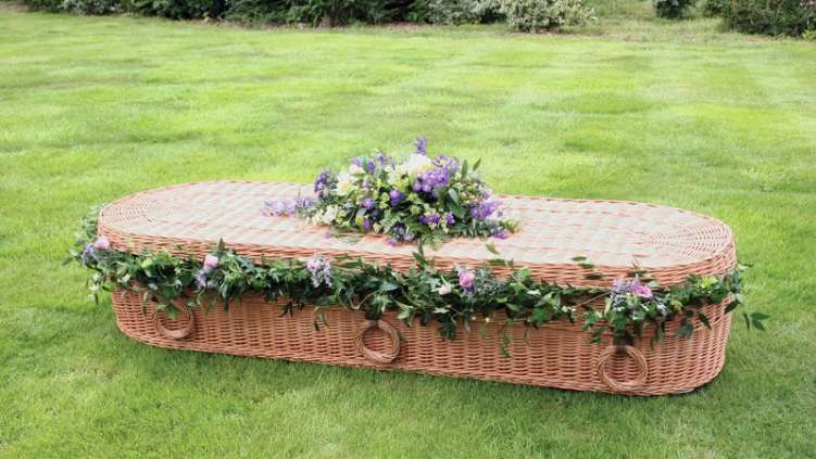 eco coffin with a floral garland and coffin spray.