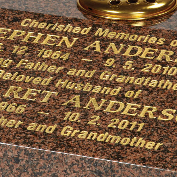 Close up of gold inscription on brown stone