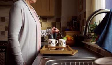 Lady making cups of tea in her kitchen.