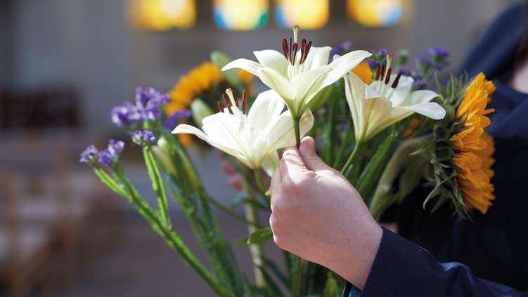 Funeral flower arrangement being held by a funeral director
