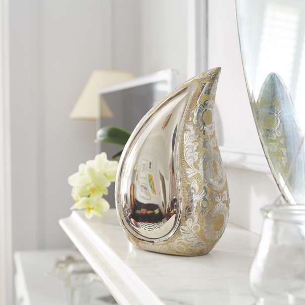 Silver coloured teardrop urn on a white mantelpiece