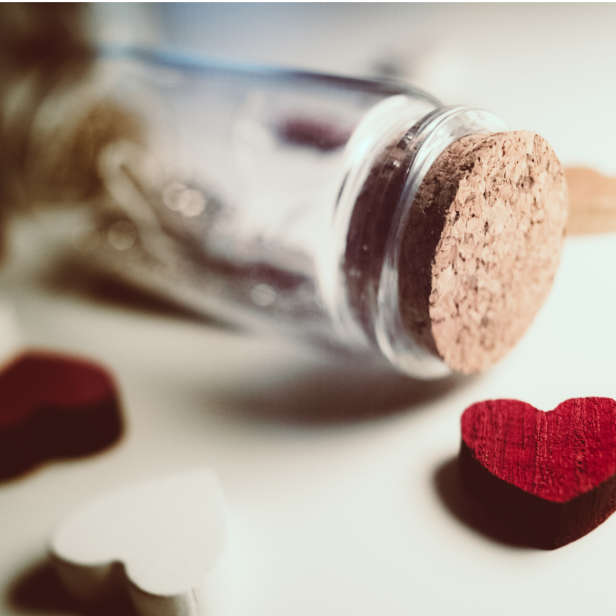 Glass corked jar on its side surrounded by red and white heart charms