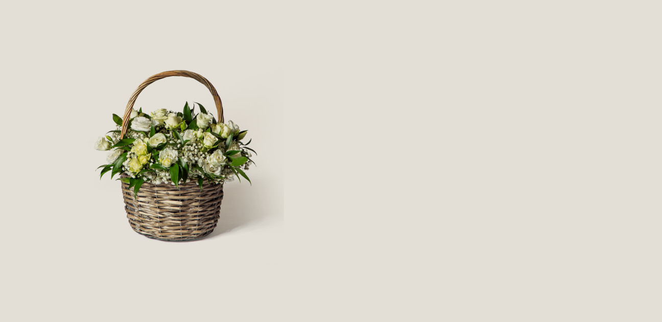 Flower arrangement in a basket with white flowers and green foliage