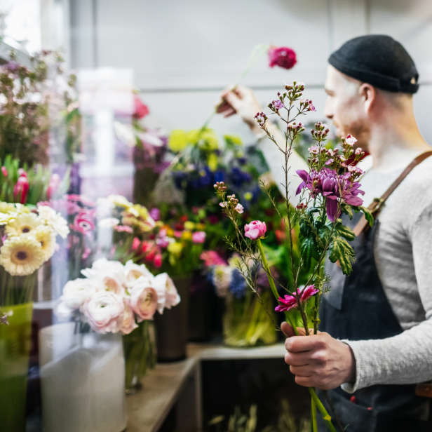 Person in a black hat and apron selecting flowers for a brightly coloured bouquet