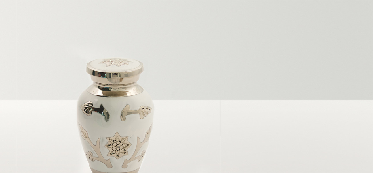 Close up of a white urn with silver floral decoration and rim