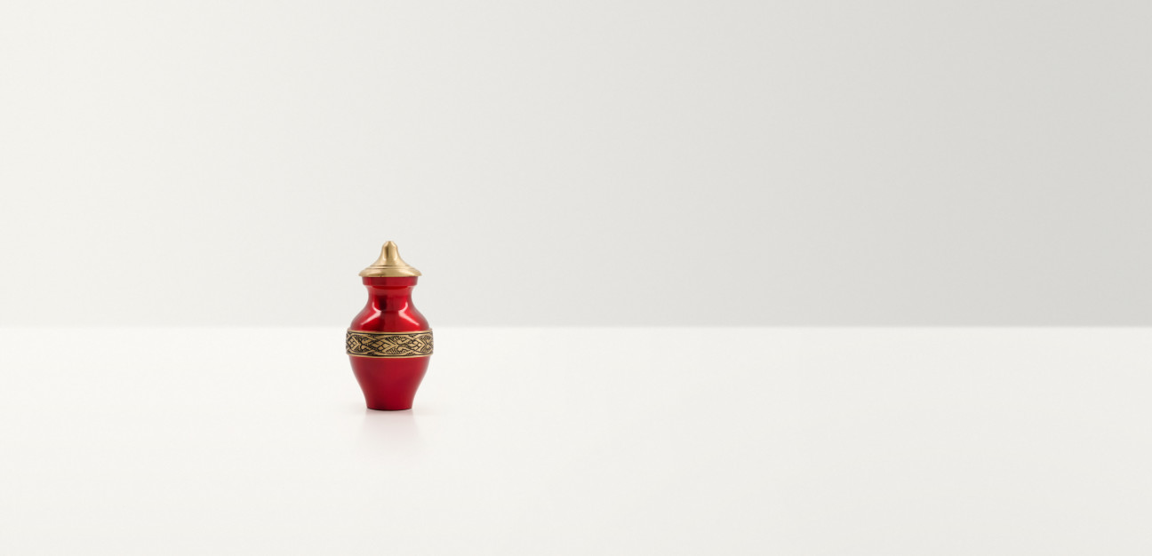 Red urn with gold band on the shoulders and lid