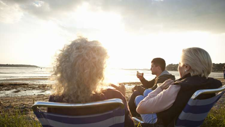 Family sat around in chairs on a beach watching the sunset.