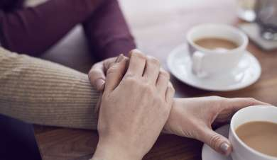 Family members holding hands providing support whilst having a cup of tea.