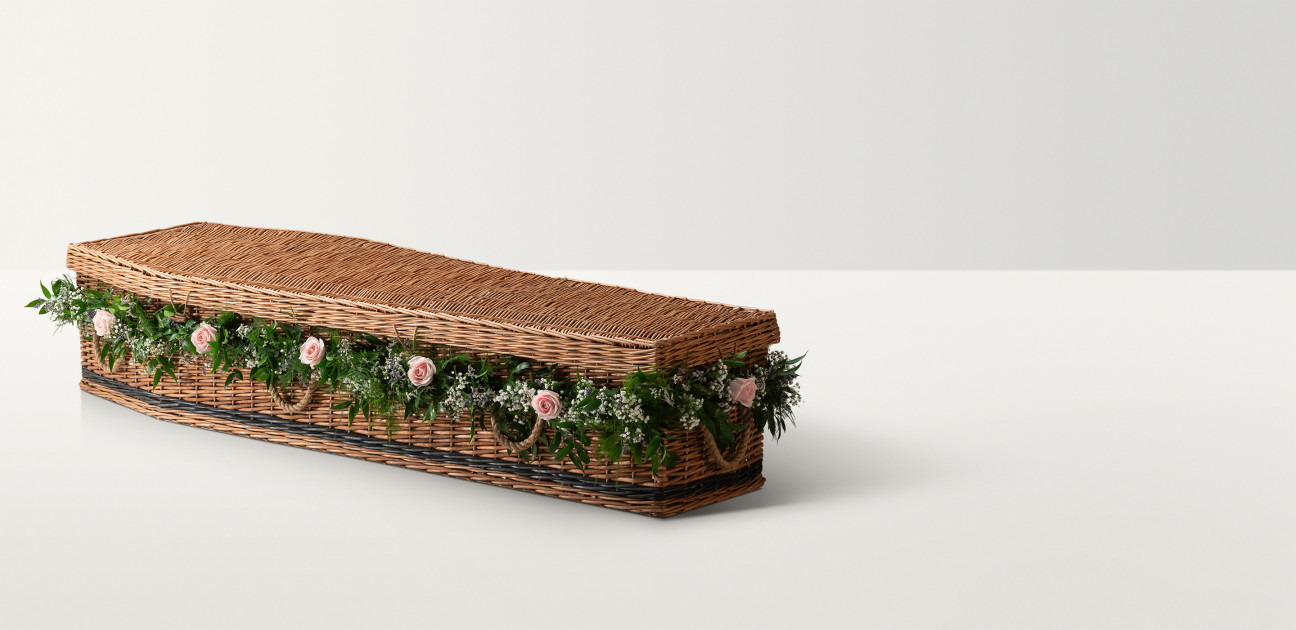 Full length image of the willow coffin in a natural colour with a floral garland