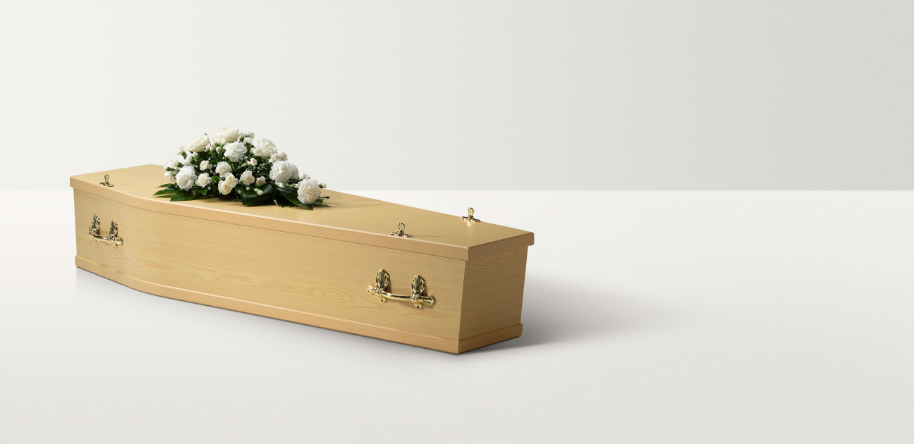 Full length image of a maple coffin with brass handles and closures and a white rose spray