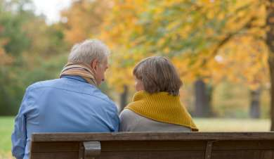 Couple sitting on a bench in a park.