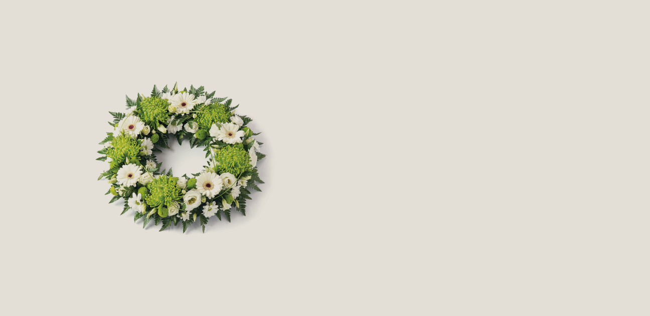 Wreath shaped floral arrangement with green and white flowers