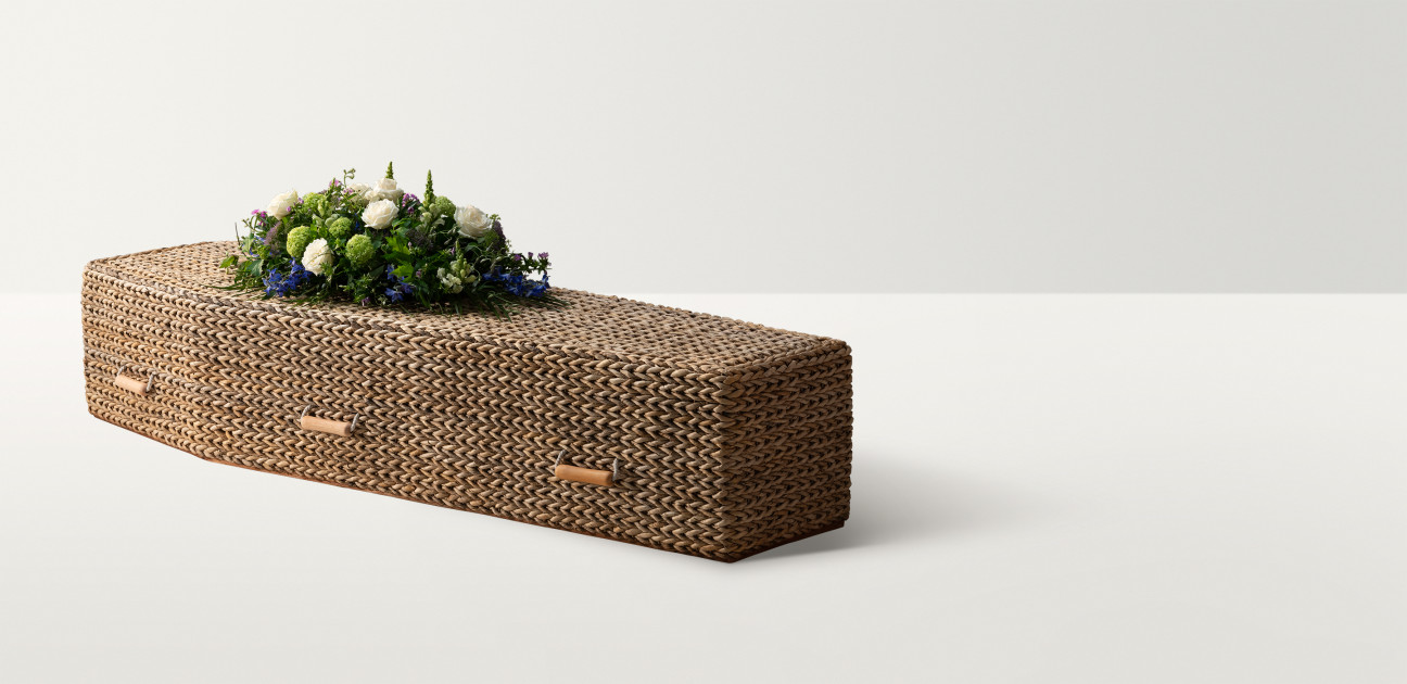 Woven water hyacinth coffin with wooden handles and white rose floral arrangement