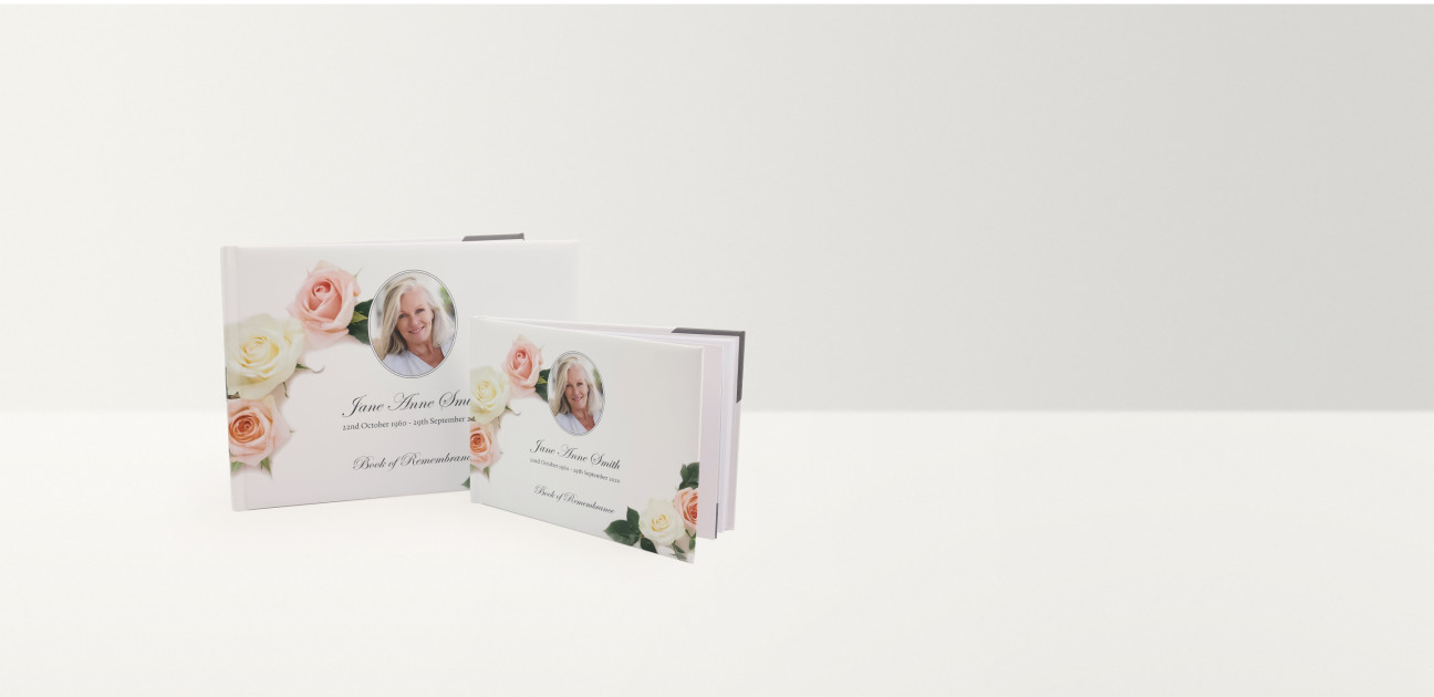 Two white books of remembrance in two sizes printed with photographs and text