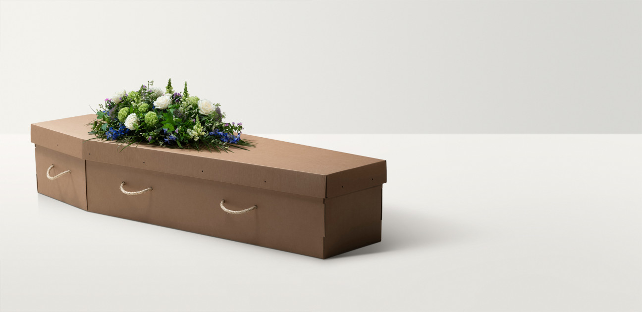 Plain brown cardboard coffin with cord handles and a floral arrangement on top