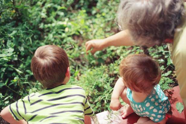 Two children look at a garden with a woman pointing