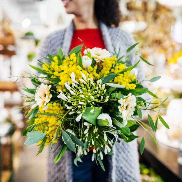 Yellow and white bouquet in a vase in front of a person in a red top and grey cardigan
