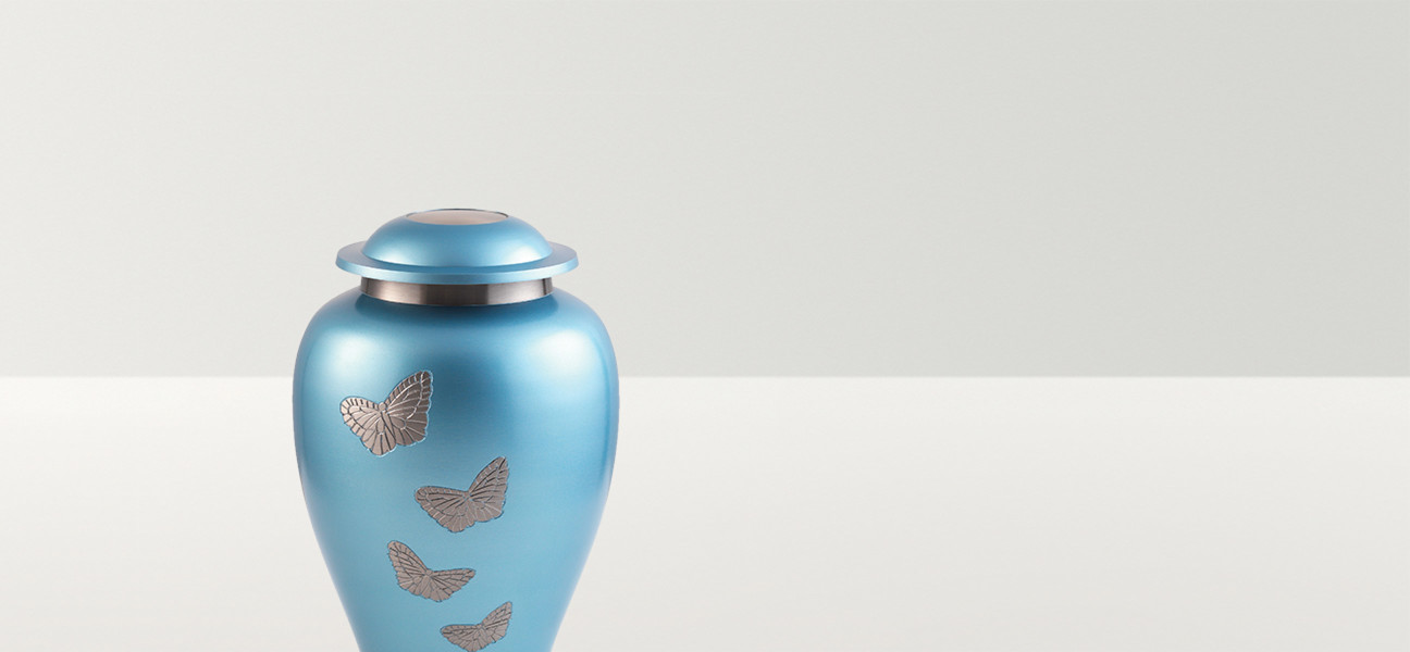 Close up of pale blue urn with silver butterflies and decoration