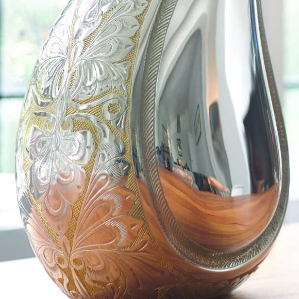 Close up image of the decoration on a silver teardrop urn