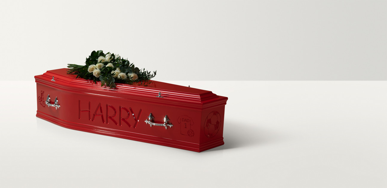 Full length image of a red wooden coffin with 'Harry' engraved on the side and a rose spray
