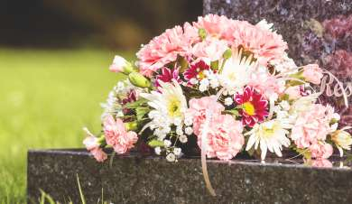 Pink and white flowers laid on a black granite gravestone.
