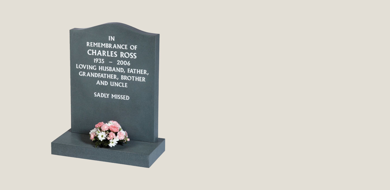 Black memorial with white inscription and pink floral arrangement