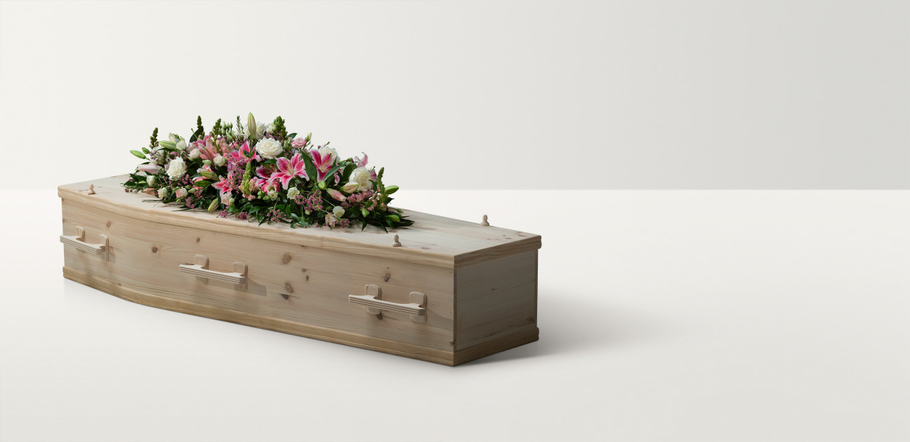 Full length image of a pine coffin with a large bright floral arrangement