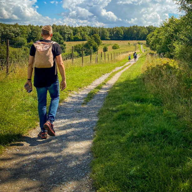 Short haired person with a canvas backpack walking down a country lane