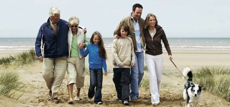 Family walking on a beach with a dog.