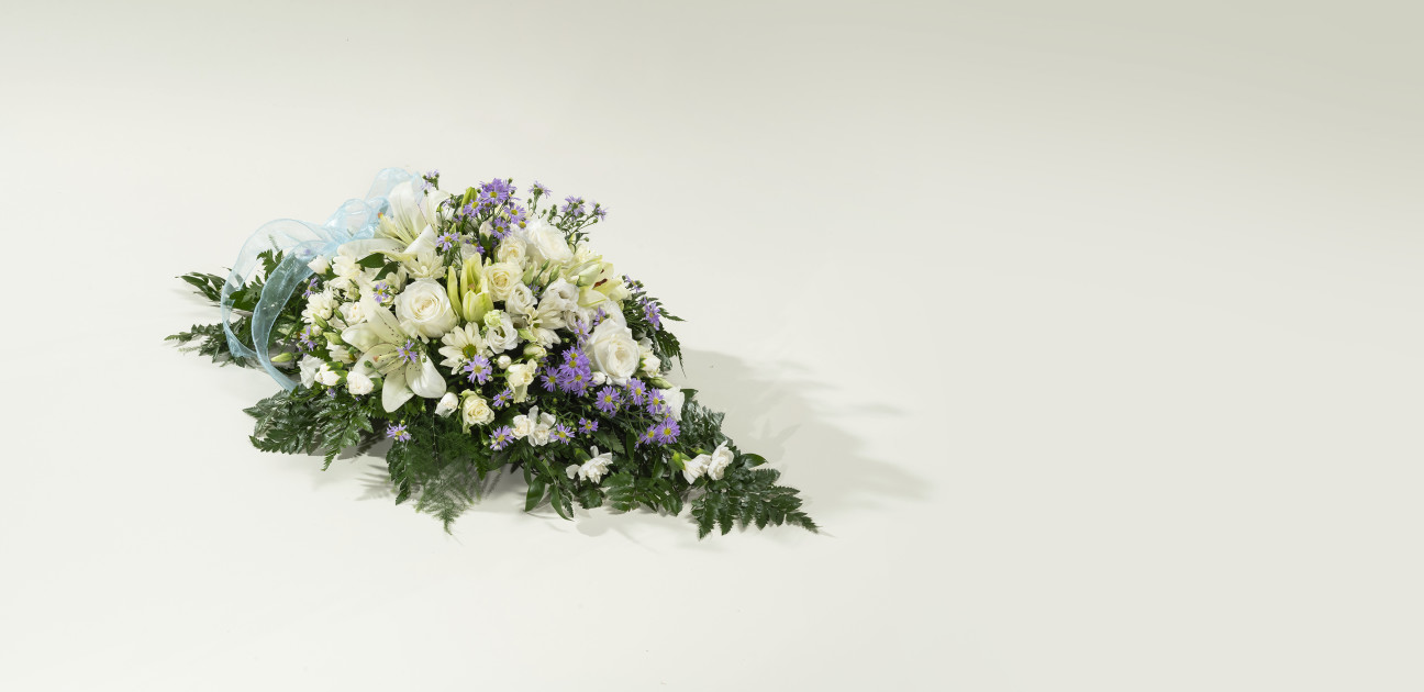 Small spray floral arrangement with white and purple flowers on green foliage