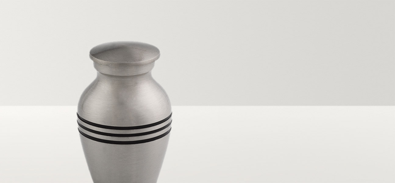 Close up of silver urn with three black stripes