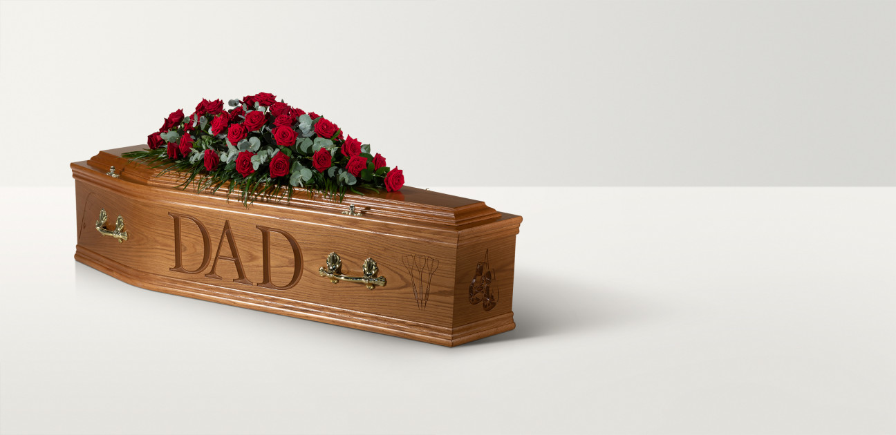 Full length image of a wooden coffin with 'Dad' engraved on the side and a rose spray