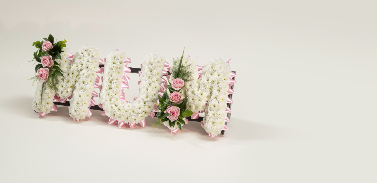 White and pink flowers spelling out the word 'Mum'