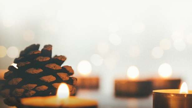 tea light candles and pine cones in soft light.