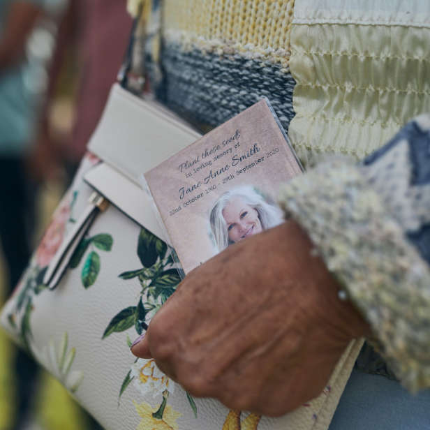 Hand holding a printed card against a cream handbag with flowers