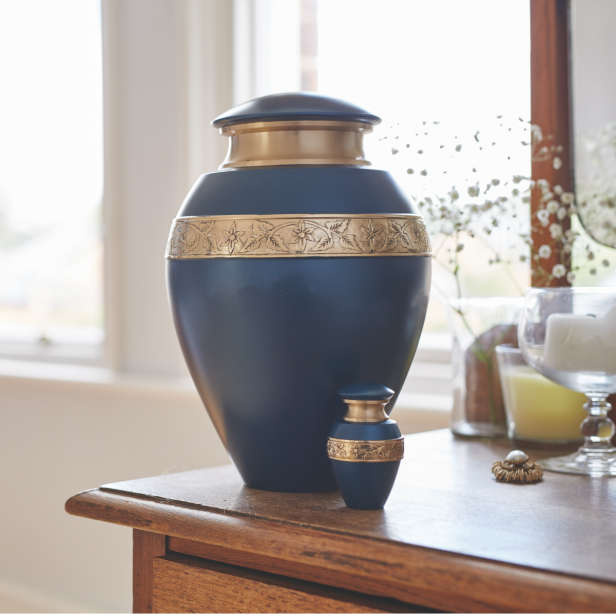 Blue urn with gold ornamentation in two sizes on a wooden sideboard