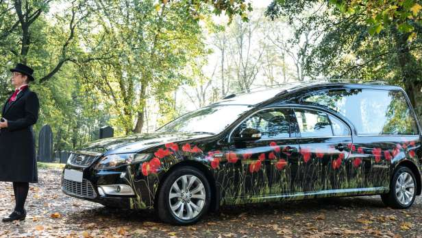 Black hearse with poppies on parked in a woodland with an attendant in front