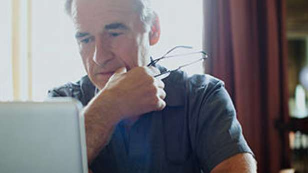 man holding his glasses, using his laptop