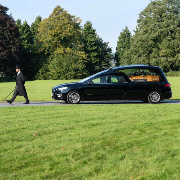 Black Hearse and attendant driving through parkland