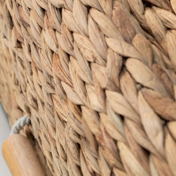 Close up of woven banana coffin with cord and wooden handles
