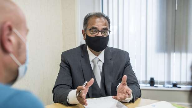 Funeral director in a mask sat at table