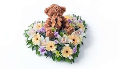 Heart with a teddy in the middle of the floral arrangement.