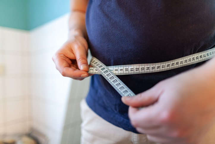 Man measures his abdomen with a measuring tape