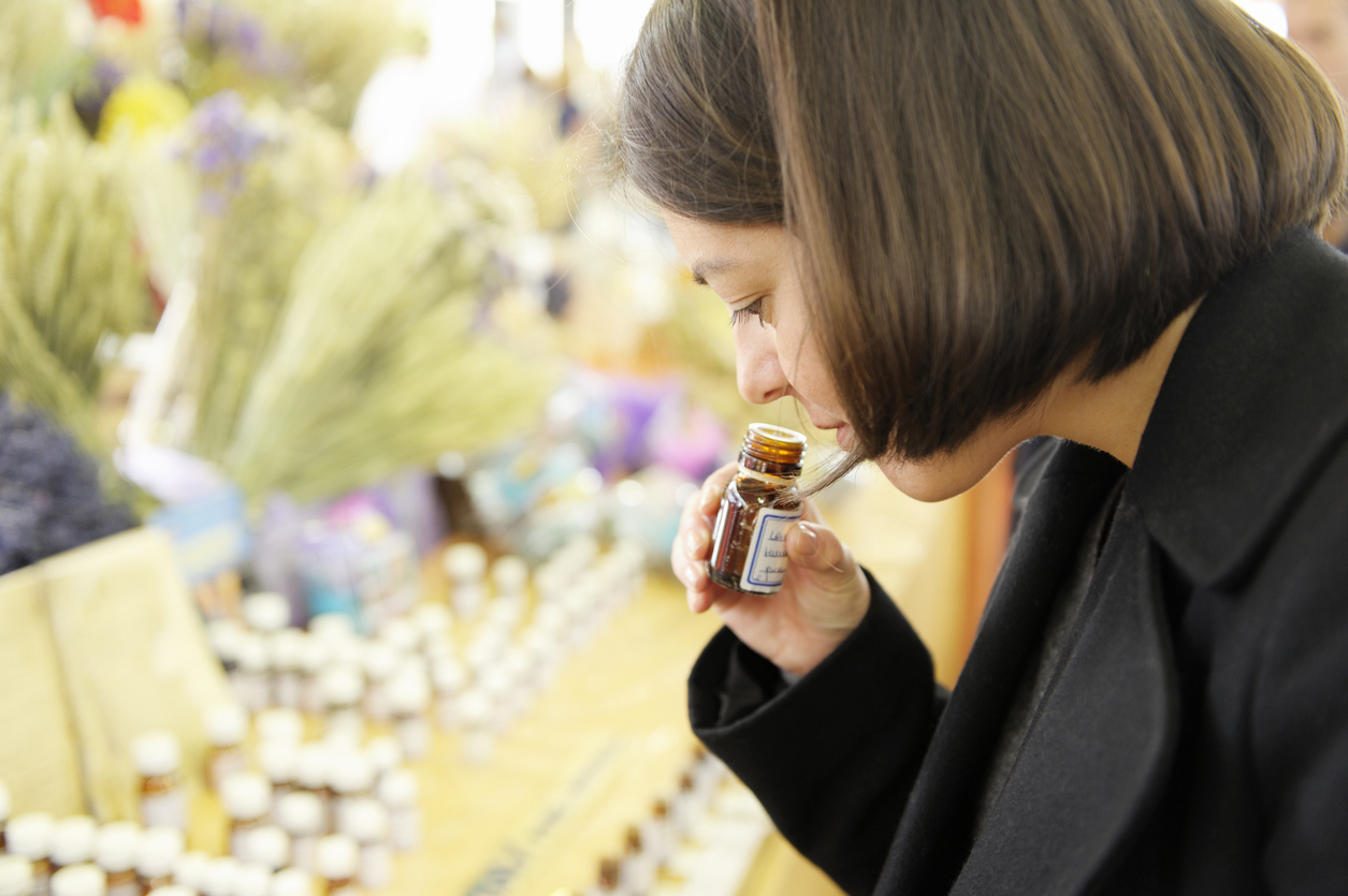 A young woman smells lavender essential oil from a bottle